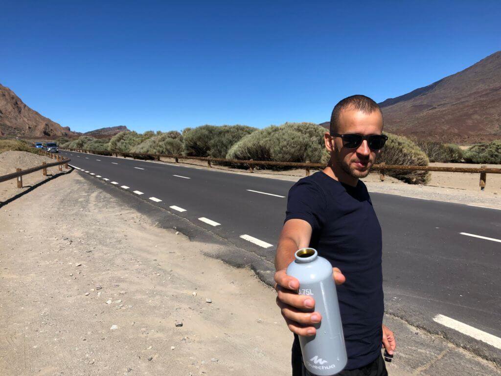 droga, mężczyzna podający butelkę wody, góry